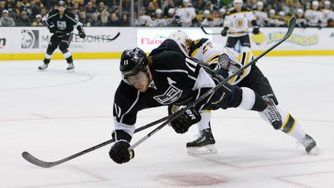 Jan 9, 2014; Los Angeles, CA, USA; Los Angeles Kings center Anze Kopitar (11) is tripped by Boston Bruins left wing Shawn Thornton (22) in the first period at Staples Center. Mandatory Credit: Kirby Lee-USA TODAY Sports
