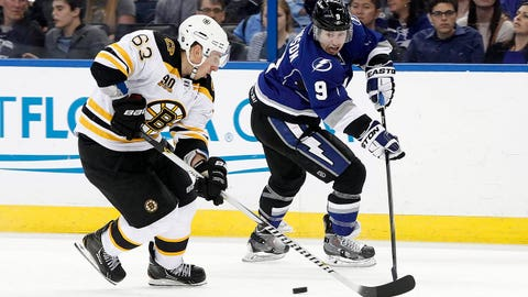 Mar 8, 2014; Tampa, FL, USA; Tampa Bay Lightning center Tyler Johnson (9) passes the puck as Boston Bruins left wing Brad Marchand (63) defends during the second period at Tampa Bay Times Forum. Mandatory Credit: Kim Klement-USA TODAY Sports