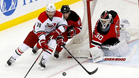 Carolina Hurricanes right wing Patrick Dwyer (39) competes for the puck with New Jersey Devils defenseman Andy Greene (6) as goalie Martin Brodeur protects his net during the third period of an NHL hockey game, Saturday, March 8, 2014, in Newark, N.J. The Devils won 5-4. (AP Photo/Julio Cortez)