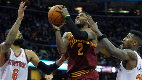 Mar 8, 2014; Cleveland, OH, USA; Cleveland Cavaliers point guard Kyrie Irving (2) drives between New York Knicks center Tyson Chandler (6) and shooting guard Iman Shumpert (21) in the fourth quarter at Quicken Loans Arena. Mandatory Credit: David Richard-USA TODAY Sports
