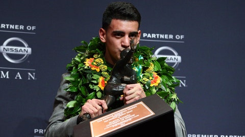 Dec 13, 2014; New  York, NY, USA; Oregon Ducks quarterback Marcus Mariota kisses the Heisman Trophy during a press conference at the New York Marriott Marquis after winning the Heisman Trophy. Mandatory Credit: Brad Penner-USA TODAY Sports