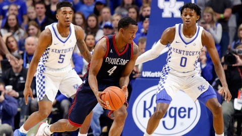 Duquesne's Rene Castro looks for an opening near Kentucky defenders Malik Monk (5) and De'Aaron Fox (0) during the first half of an NCAA college basketball game, Sunday, Nov. 20, 2016, in Lexington, Ky. (AP Photo/James Crisp)
