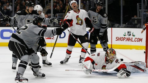 Los Angeles Kings center Trevor Lewis, left, reacts after scoring against Ottawa Senators goalie Mike Condon, right, with right wing Dustin Brown (23), and center Anze Kopitar (11), of Slovenia, also reacting with defenseman Marc Methot (3) during the second period of an NHL hockey game in Los Angeles, Saturday, Dec. 10, 2016. (AP Photo/Alex Gallardo)