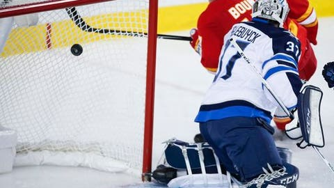Winnipeg Jets goalie Connor Hellebuyck, right, looks back as Calgary Flames' Lance Bouma scores during the third period of an NHL hockey game in Calgary, Alberta, Saturday, Dec. 10, 2016. (Jeff McIntosh/The Canadian Press via AP)