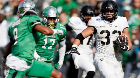 Army running back Darnell Woolfolk (33) looks for room against North Texas defensive back Nate Brooks (9) during the first half of the Heart of Dallas Bowl NCAA college football game Tuesday, Dec. 27, 2016 in Dallas. (AP Photo/Brandon Wade)