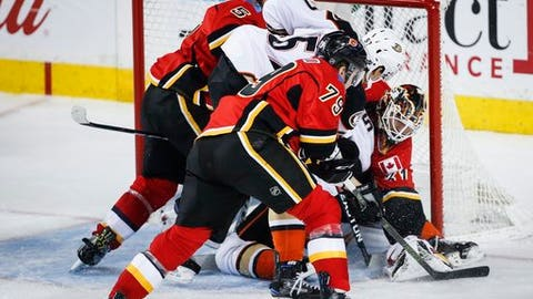 Anaheim Ducks' Rickard Rakell, center, from Sweden, scores on Calgary Flames goalie Chad Johnson during the third period of an NHL hockey game in Calgary, Alberta, Thursday, Dec. 29, 2016. (Jeff McIntosh/The Canadian Press via AP)
