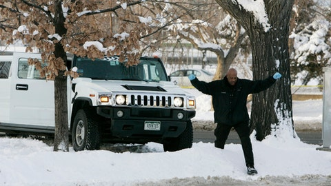 FILE - In this Monday, Jan. 1, 2007, file photo, a Denver Police Department investigator climbs over a snowbank next to a limousine in which Denver Broncos cornerback Darrent Williams was shot and killed in downtown Denver. New Year's Day marks the 10-year anniversary of Williams' death following a confrontation between Broncos players and gang members at a nightclub. (AP Photo/Ed Andrieski, File)