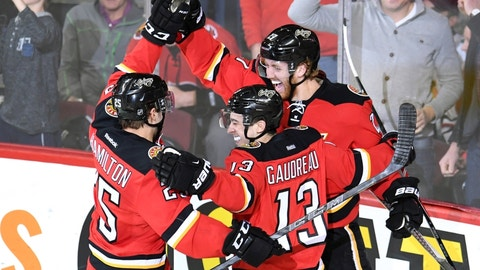 Mar 26, 2016; Calgary, Alberta, CAN; Calgary Flames defenseman Dougie Hamilton (27) celebrates his second period goal with centre Freddie Hamilton (25) and left wing Johnny Gaudreau (13) against the Chicago Blackhawks at Scotiabank Saddledome. Mandatory Credit: Candice Ward-USA TODAY Sports