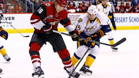 Arizona Coyotes center Christian Dvorak (18) and Nashville Predators right wing Craig Smith (15) battle for the puck during the second period of an NHL hockey game Saturday, Dec. 10, 2016, in Glendale, Ariz. (AP Photo/Ross D. Franklin)