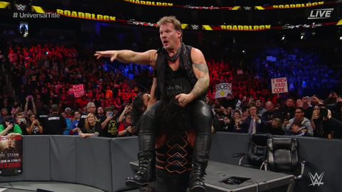 Seth Rollins and Roman Reigns put Chris Jericho through an announce table