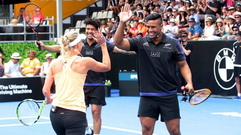 Denmark's Caroline Wozniacki celebrates with All Black player's Julian Savea, right, and his brother Ardie during an exhibition event ahead of the ASB Classic tennis tournament in Auckland, New Zealand, Sunday, Jan. 1, 2017. (Doug Sherring/New Zealand Herald via AP)