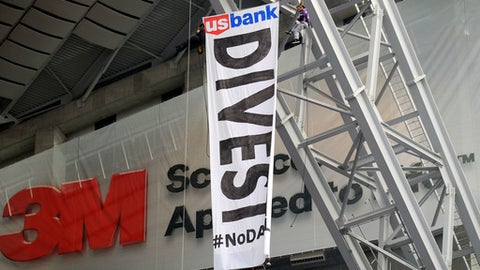 Protestors against the Dakota Access Pipeline repel from the catwalk in U.S. Bank Stadium during the first half of an NFL football game between the Minnesota Vikings and the Chicago Bears, Sunday, Jan. 1, 2017, in Minneapolis. (AP Photo/Andy Clayton-King)