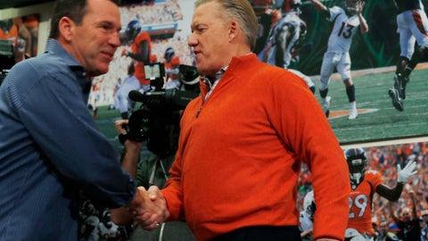 Gary Kubiak, left, shakes hands with Denver Broncos general manager John Elway as Kubiak heads to the podium to step down as head coach of the Broncos because of health concerns Monday, Jan. 2, 2017, at team headquarters in Englewood, Colo. (AP Photo/David Zalubowski)