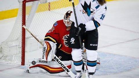 San Jose Sharks' Joe Thornton, right, screens Calgary Flames goalie Chad Johnson on a shot during the second period of an NHL hockey game Wednesday, Jan. 11, 2017, in Calgary, Alberta. (Jeff McIntosh/The Canadian Press via AP)