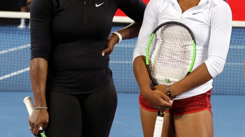 United States' Serena Williams, left, talks with Australian player Destanee Aiava during a promotional event on Margaret Court Arena ahead of the Australian Open tennis championships in Melbourne, Australia, Thursday, Jan. 12, 2017. Aiava will be the first player born this century to play in the main draw match at a tennis major. (AP Photo/Mark Baker)