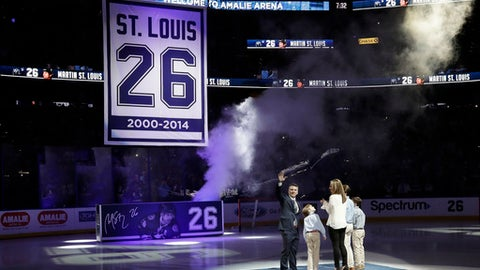 Former Tampa Bay Lightning right winger Martin St. Louis waves as he stands with his family as a banner bearing his number is raised during jersey retirement ceremony before an NHL hockey game between the Lightning and the Columbus Blue Jackets on Friday, Jan. 13, 2017, in Tampa, Fla. (AP Photo/Chris O'Meara)
