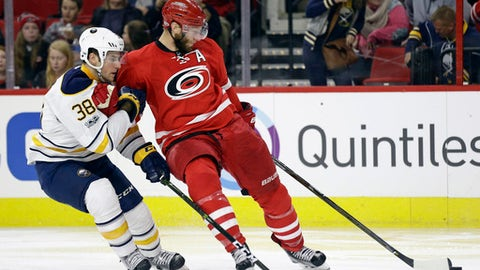 Buffalo Sabres' Taylor Fedun (38) and Carolina Hurricanes' Jordan Staal (11) chase the puck during the second period of an NHL hockey game in Raleigh, N.C., Friday, Jan. 13, 2017. (AP Photo/Gerry Broome)
