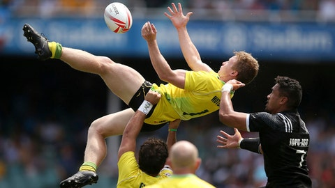 Australia's Charlie Taylor, top center, and New Zealand's Iopu Iopu-Aso, right, compete for the ball during their match at the World Rugby Sevens Series tournament in Sydney, Saturday, Feb. 4, 2017. (AP Photo/Rick Rycroft)