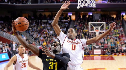 Oregon guard Dylan Ennis, center, shoots as Southern California guard Shaqquan Aaron, right, defends along with forward Bennie Boatwright during the second half of an NCAA college basketball game, Saturday, Feb. 11, 2017, in Los Angeles. Oregon won 81-70. (AP Photo/Mark J. Terrill)