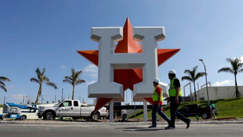 Workers walk past the Houston Astros team logo outside an entrance at the Ballpark of the Palm Beaches, the new spring training facility for the Astros and Washington Nationals, Monday, Feb. 13, 2017, in West Palm Beach, Fla. Astros pitchers and catchers are scheduled to report Tuesday.(AP Photo/David J. Phillip)