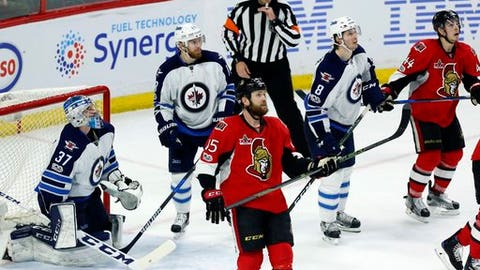 Ottawa Senators and Winnipeg Jets players look up at the replay as a play during the last seconds of the game was under review during third period NHL hockey action in Ottawa, Sunday Feb. 19, 2017. (Fred Chartrand/The Canadian Press via AP)