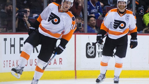 Philadelphia Flyers' Brayden Schenn, left, and Claude Giroux celebrate Schenn's goal against the Vancouver Canucks during the second period of an NHL hockey game in Vancouver, British Columbia, Sunday, Feb. 19, 2017. (Darryl Dyck/The Canadian Press via AP)