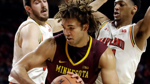 Minnesota center Reggie Lynch, center, is pressured by Maryland forwards Ivan Bender, left, and Justin Jackson durkng the first half of an NCAA college basketball game, Wednesday, Feb. 22, 2017, in College Park, Md. (AP Photo/Patrick Semansky)