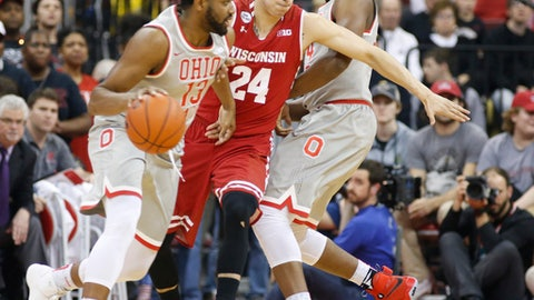 Wisconsin's Bronson Koenig, center, fights through a pick set by Ohio State's Andre Wesson, right, as JaQuan Lyle looks for an open pass during the first half of an NCAA college basketball game Thursday, Feb. 23, 2017, in Columbus, Ohio. (AP Photo/Jay LaPrete)