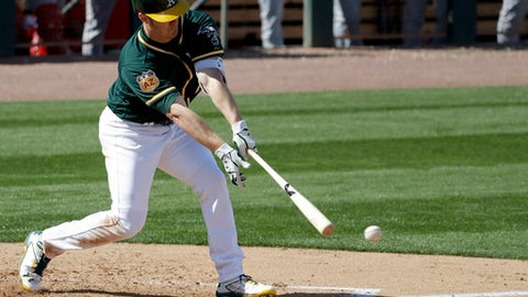 Oakland Athletics first baseman Mark Canha hits a RBI-double against the Los Angeles Angels during the third inning of a spring baseball game in Mesa, Ariz., Sunday, Feb. 26, 2017. (AP Photo/Chris Carlson)