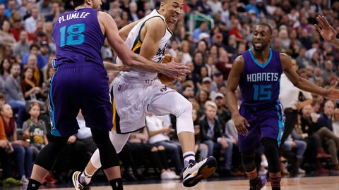 Feb 4, 2017; Salt Lake City, UT, USA; Utah Jazz guard Dante Exum (11) drives to the hoop against Charlotte Hornets center Miles Plumlee (18) and guard Kemba Walker (15) in the third quarter at Vivint Smart Home Arena. Utah Jazz defeated the Charlotte Hornets 105-98. Mandatory Credit: Jeff Swinger-USA TODAY Sports