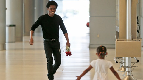 Olympic silver medalist Feyisa Lilesa, left, of Ethiopia, runs to meet his daughter Soko, 5, while picking up his family at Miami International Airport, Tuesday, Feb. 14, 2017, in Miami. Lilesa  arrived in the U.S. on a special skills visa, which allows him to train and compete until January. His wife, son, daughter and brother joined him in Miami Tuesday. (AP Photo/Wilfredo Lee)
