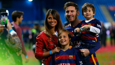 Barcelona's Lionel Messi, carrying his son, posses for a photo with his wife Antonella Roccuzzo as they celebrate after winning the final of the Copa del Rey soccer match between FC Barcelona and Sevilla FC at the Vicente Calderon stadium in Madrid, Sunday, May 22, 2016. Barcelona won 2-0 (AP Photo/Francisco Seco)