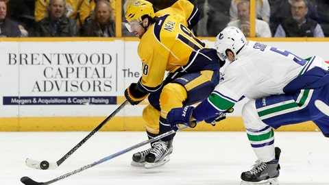 Nashville Predators right wing James Neal (18) is defended by Vancouver Canucks' Luca Sbisa (5), of Italy, during the second period of an NHL hockey game Tuesday, Feb. 7, 2017, in Nashville, Tenn. (AP Photo/Mark Humphrey)
