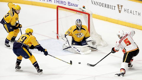 Calgary Flames defenseman Mark Giordano (5) scores the winning goal against Nashville Predators goalie Juuse Saros (74), of Finland, during overtime in an NHL hockey game Tuesday, Feb. 21, 2017, in Nashville, Tenn.  Also defending for the Predators are Filip Forsberg (9), of Sweden; and Roman Josi (59), of Switzerland. The Flames won 6-5. (AP Photo/Mark Humphrey)