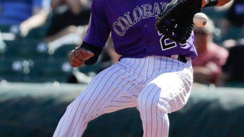 Colorado Rockies first baseman Ian Desmond fields a ball hit by Seattle Mariners' Leonys Martin during first inning at a spring baseball game in Scottsdale, Ariz., Saturday, March 4, 2017. (AP Photo/Chris Carlson)