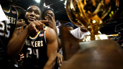 Wichita State's Shaquille Morris celebrates as he is handed the trophy following an NCAA college basketball game after defeating Illinois State 71-51 to win the championship of the Missouri Valley Conference men's tournament Sunday, March 5, 2017, in St. Louis. (AP Photo/Jeff Roberson)
