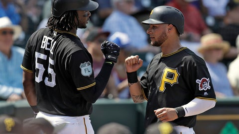 Pittsburgh Pirates' Danny Ortiz, right, high fives on-deck batter Josh Bell after scoring on a ground out by Alen Hanson during the second inning of an exhibition baseball game against the Dominican Republic Wednesday, March 8, 2017, in Bradenton, Fla. (AP Photo/Chris O'Meara)