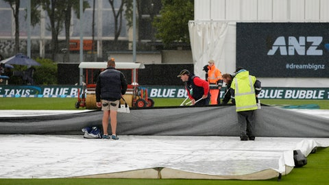 Ground staff clear surface water from the covers as rain delays play on the final day of the first cricket test between South Africa and New Zealand at University Oval, Dunedin, New Zealand, Sunday, March 12, 2017. (AP Photo/Mark Baker)