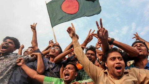 Bangladeshi cricket fans wave their national flag and cheer after the Bangladesh cricket team clinched a historic four-wicket win against Sri Lanka in their 100th test match, as they celebrate in Dhaka, Bangladesh, Sunday, March 19, 2017. The Bangladesh team also had their first ever test victory against Sri Lanka, to secure a series draw Sunday. (AP Photo/Rajib Dhar)