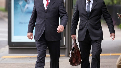 Adrian Gard, left, a 51-year-old Australian who has done work for New Zealand's rugby union team for more than 10 years, arrives at the Waverley Local Court in Sydney, Tuesday, March 21, 2017. Gard, security consultant for the New Zealand All Blacks has denied making a false statement to police after a listening device was found in a meeting room at the team's hotel in Sydney before a rugby test against Australia last August. (AP Photo/Rick Rycroft)