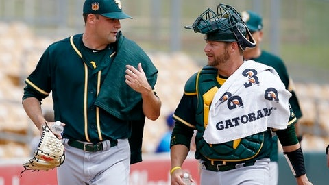 Oakland Athletics pitcher Andrew Triggs, left, talks with catcher Stephen Vogt after warming up in the bullpen prior to a spring training baseball game against the Chicago White Sox, Wednesday, March 22, 2017, in Glendale, Ariz. (AP Photo/Ross D. Franklin)