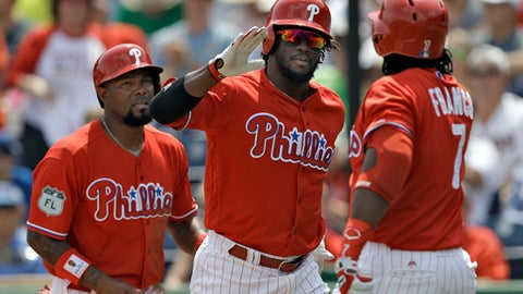 Philadelphia Phillies' Odubel Herrera, center, high fives on-deck batter Maikel Franco, right, after Herrera hit a two-run home off off Minnesota Twins' Nick Tepesch during the first inning of a spring training baseball game Thursday, March 23, 2017, in Clearwater, Fla. Phillies' Howie Kendrick, left, also scored. (AP Photo/Chris O'Meara)