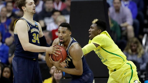 Michigan guard Zak Irvin, center, grabs a rebound in front of teammate Mark Donnal, left, and Oregon guard Dylan Ennis during the first half of a regional semifinal of the NCAA men's college basketball tournament, Thursday, March 23, 2017, in Kansas City, Mo. (AP Photo/Charlie Riedel)