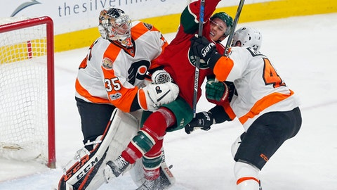 Minnesota Wild's Jared Spurgeon, center, gets squeezed between Philadelphia Flyers goalie Steve Mason, left, and Flyers' Andrew MacDonald during the third period of an NHL hockey game Thursday, March 23, 2017, in St. Paul, Minn. The Flyers won 3-1. (AP Photo/Jim Mone)