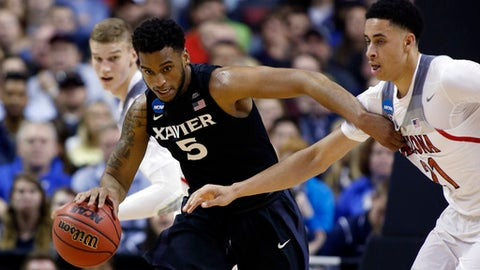 Xavier guard Trevon Bluiett (5) dribbles next to Arizona center Chance Comanche (21) during the first half of an NCAA Tournament college basketball regional semifinal game Thursday, March 23, 2017, in San Jose, Calif. (AP Photo/Tony Avelar)