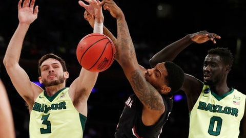 South Carolina guard Sindarius Thornwell, center, battles for a rebound against Baylor guard Jake Lindsey (3) and forward Jo Lual-Acuil Jr. (0) in the first half of an East Regional semifinal game of the NCAA men's college basketball tournament, Friday, March 24, 2017, in New York. (AP Photo/Julio Cortez)