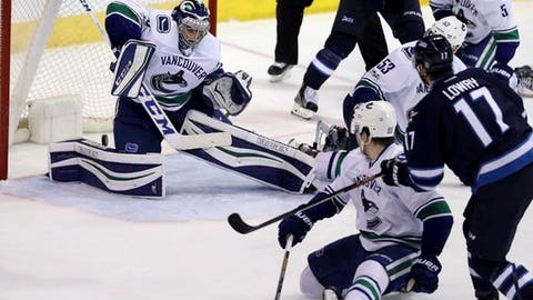 Adam Lowry (17) scores against Vancouver Canucks goaltender Ryan Miller (30) during the third period of an NHL hockey game Sunday, March 26, 2017, in Winnipeg, Manitoba. (Trevor Hagan/The Canadian Press via AP)
