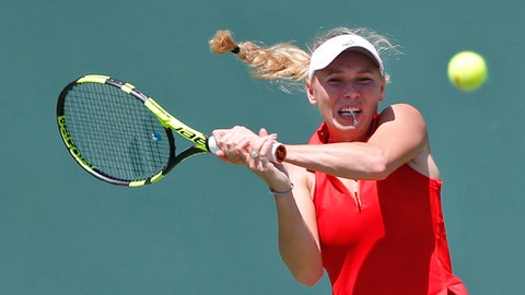 Caroline Wozniacki, of Denmark, returns a shot from Garbine Muguruza, of Spain, during a tennis match at the Miami Open, Monday, March 27, 2017 in Key Biscayne, Fla. (AP Photo/Wilfredo Lee)