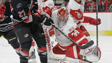 Detroit Red Wings goalie Petr Mrazek (34), of the Czech Republic, blocks Carolina Hurricanes' Justin Faulk (27) during the second period of an NHL hockey game in Raleigh, N.C., Monday, March 27, 2017. (AP Photo/Gerry Broome)
