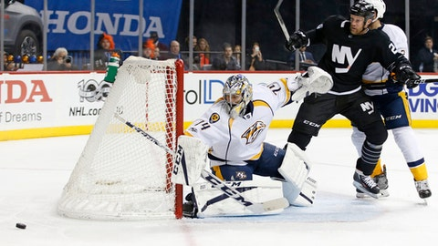 Nashville Predators defenseman Anthony Bitetto (2) defends New York Islanders left wing Jason Chimera (25) as Predators goalie Juuse Saros (74) of Finland deflects a shot in the second period of an NHL hockey game in New York, Monday, March 27, 2017. (AP Photo/Kathy Willens)